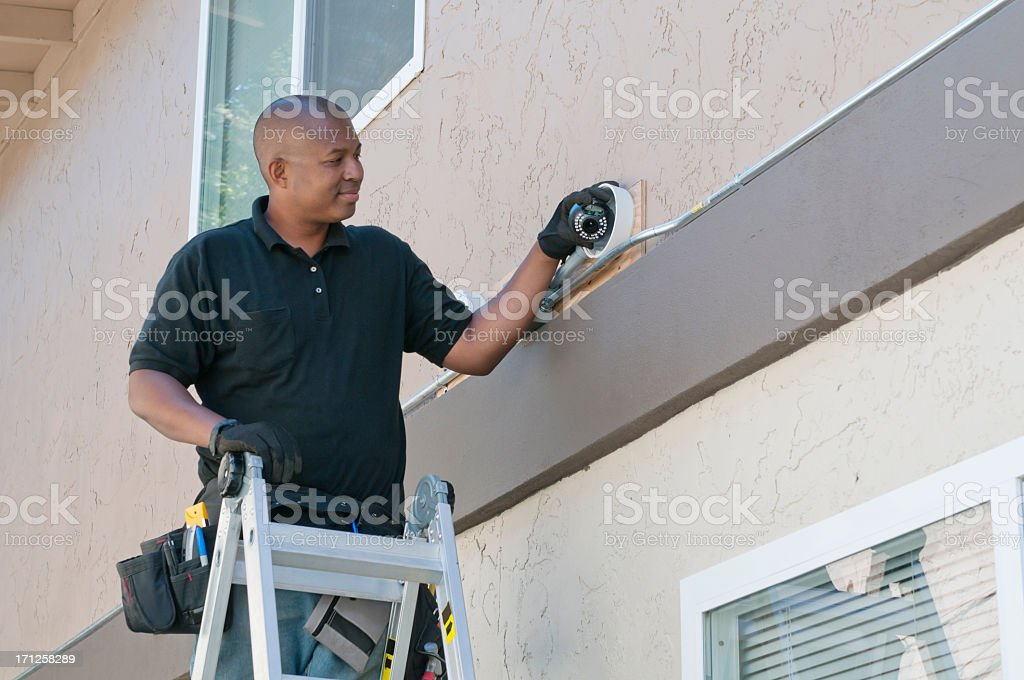 Worker standing on ladder installing security installation stock photo