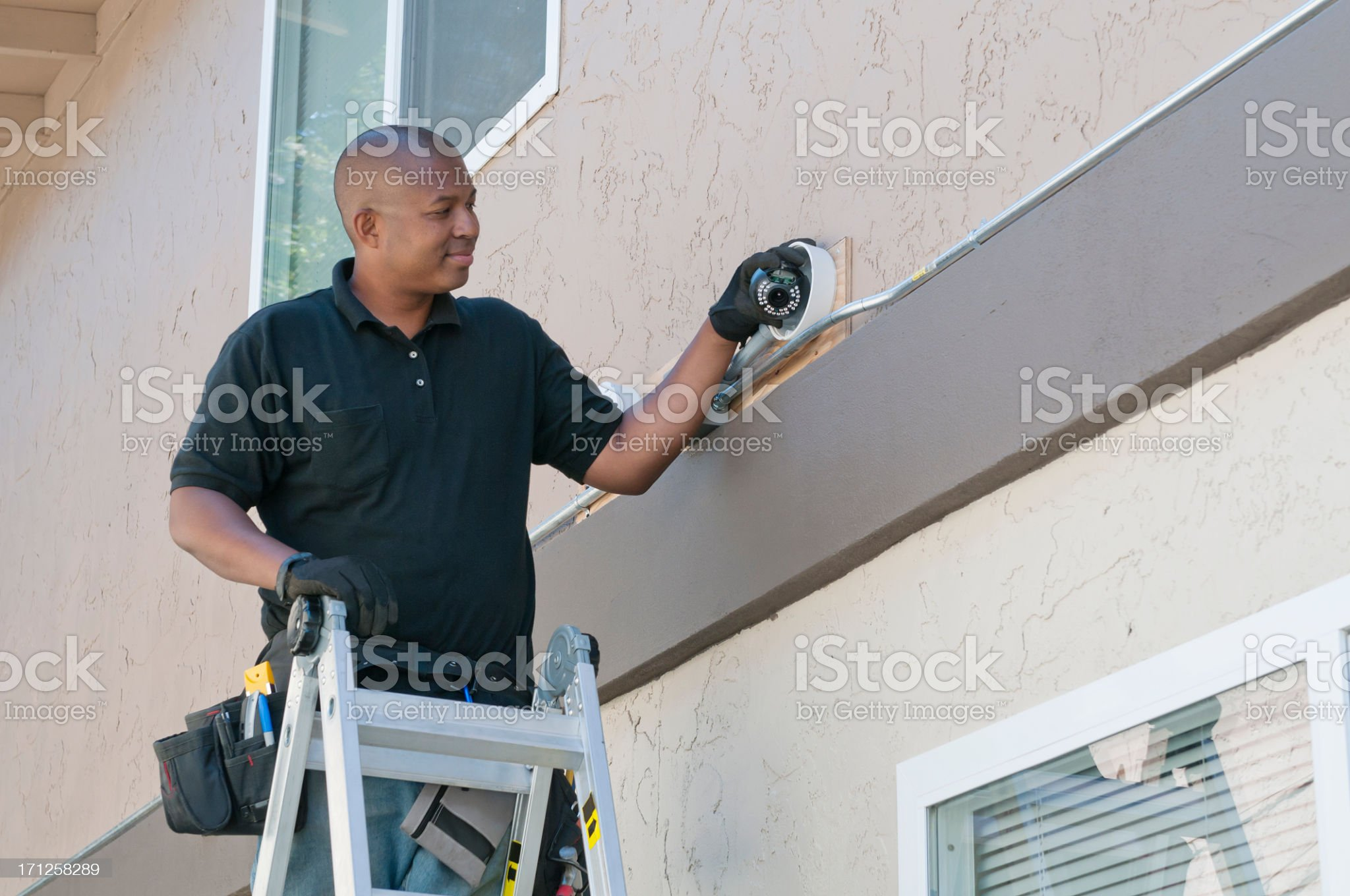 Worker standing on ladder installing security installation royalty-free stock photo