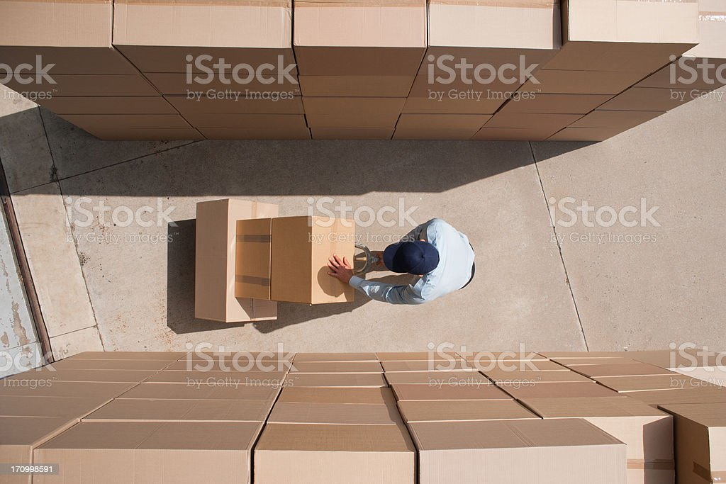 Worker standing with boxes and hand truck stock photo