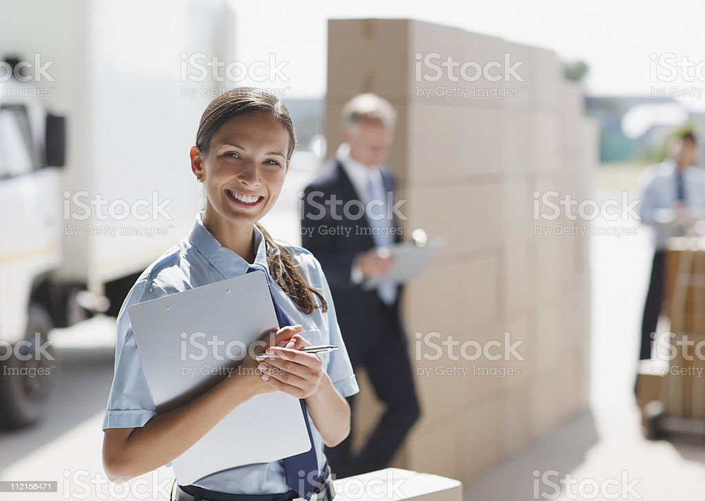 Worker standing with clipboard in shipping area royalty-free stock photo