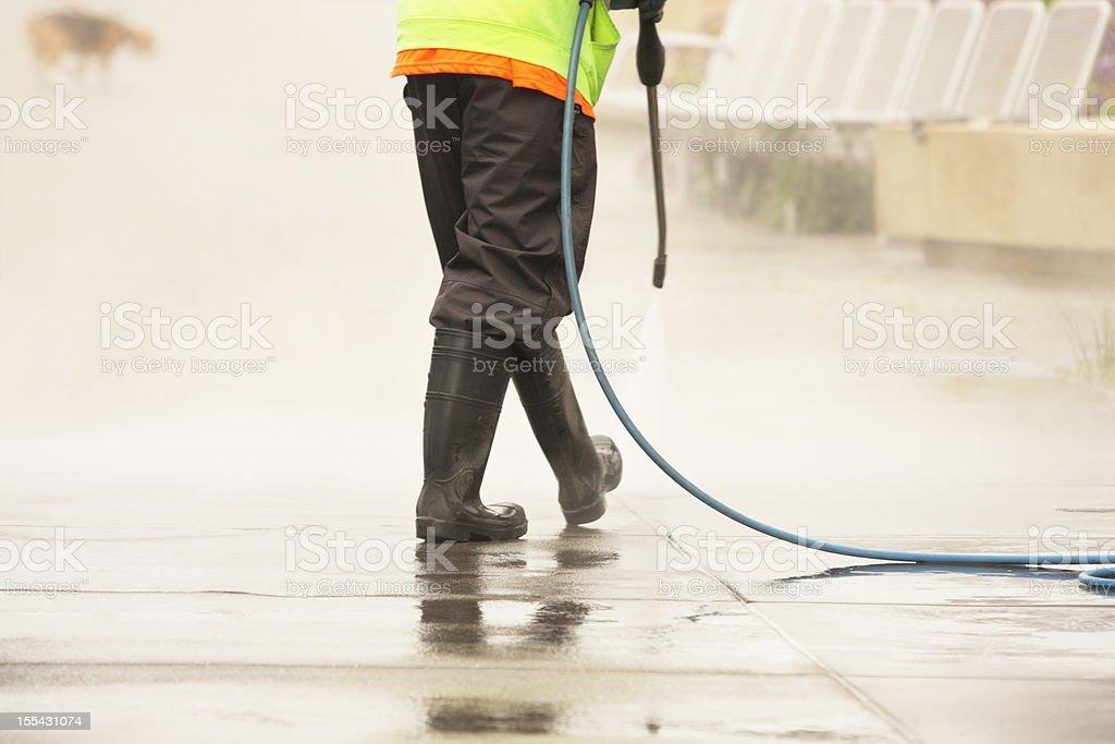 Worker Steam Cleans Sidewalk Dog stock photo