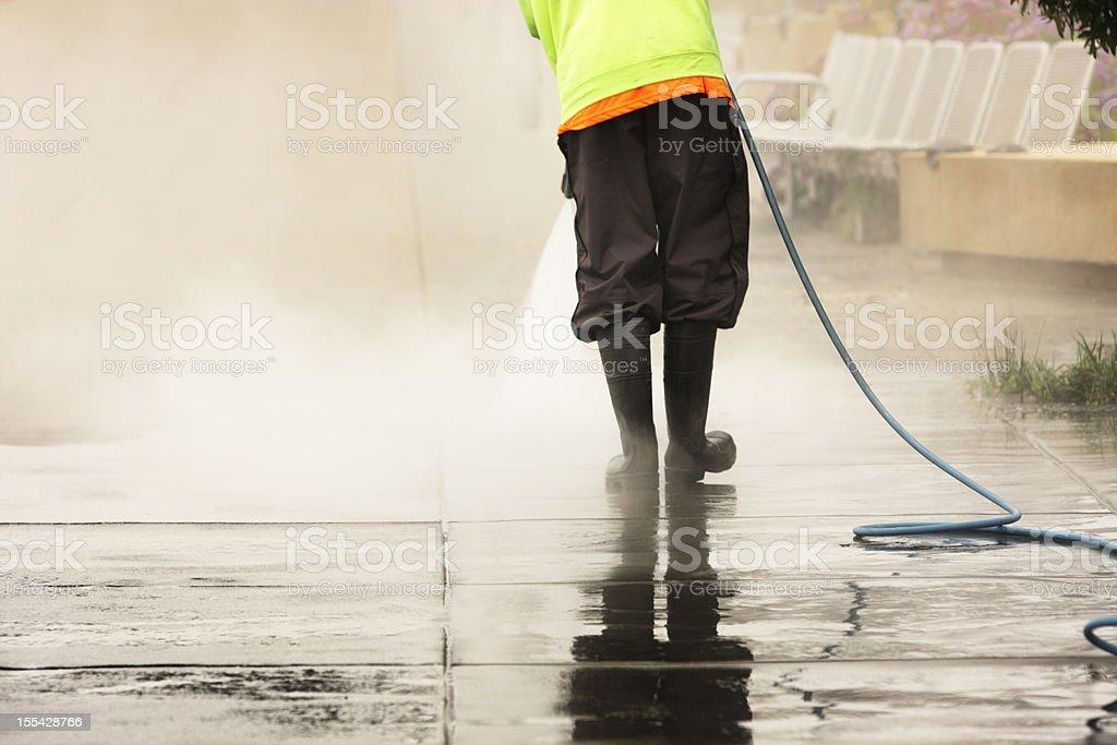 Worker Steam Cleans Sidewalk royalty-free stock photo