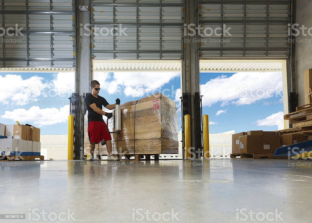worker stretch wrapping merchandise stock photo