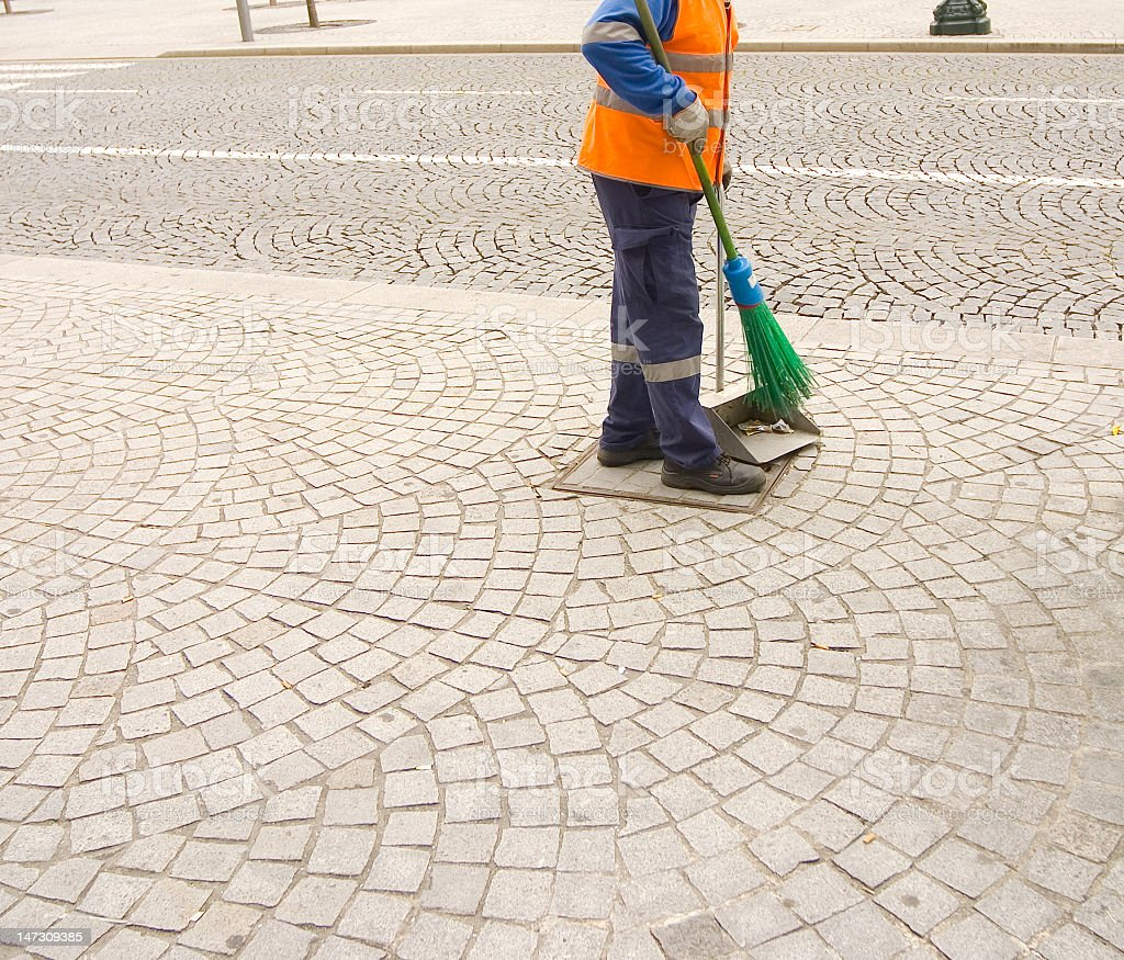 Worker sweeping the cobblestone stock photo