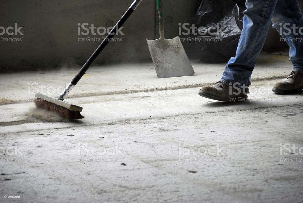 Worker Sweeping Up at Construction Site stock photo