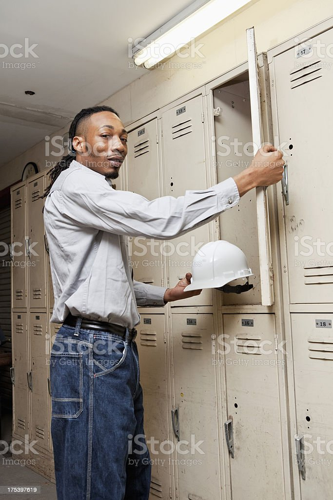 Worker taking hardhat out of locker stock photo
