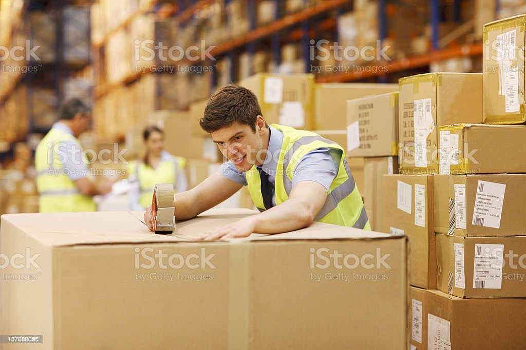 Worker taping box in warehouse stock photo