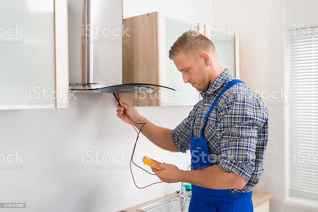 Worker Testing Kitchen Hood With Multimeter stock photo