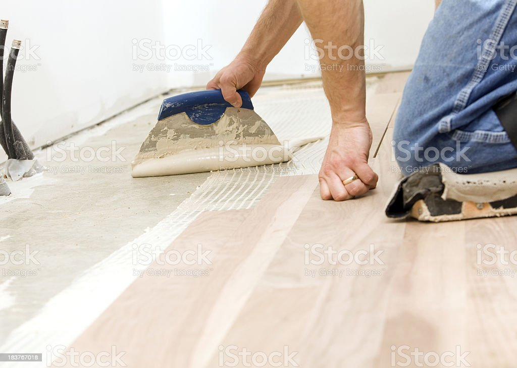 Worker Troweling Adhesive for a Hardwood Floor over Concrete stock photo