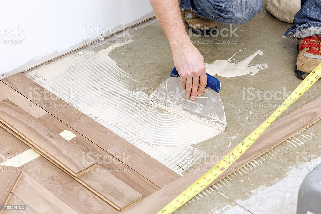 Worker Troweling Adhesive for a Hardwood over Concrete Floor stock photo