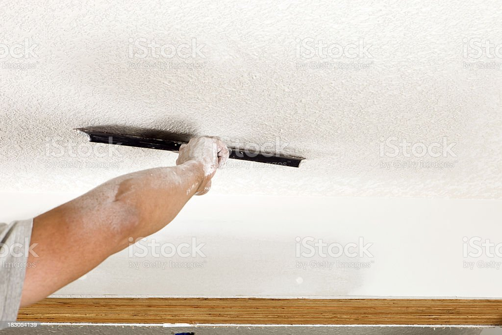 Worker Troweling Drywall Mud on a Ceiling for Knockdown Texture royalty-free stock photo