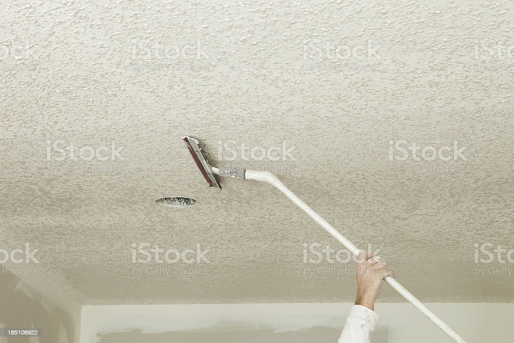 Worker Troweling Drywall Mud on a Ceiling for Knockdown Texture stock photo