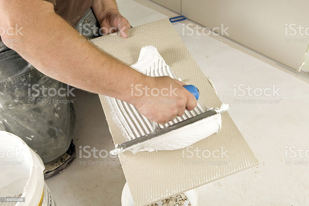 Worker Troweling Mud onto back of a Wall Tile stock photo