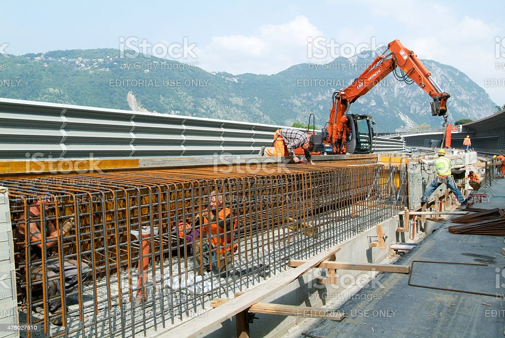 worker tying rebar for construction of a highway stock photo