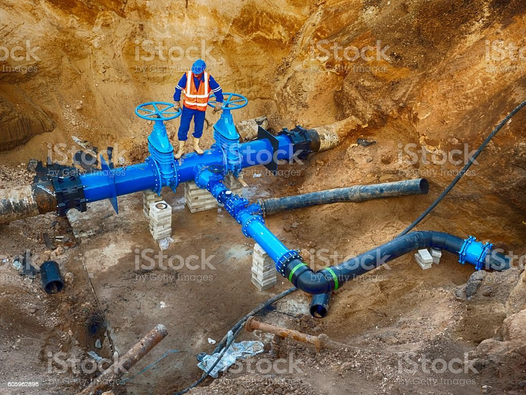 Worker underground on gate valve, reconstrucion of drink water system stock photo