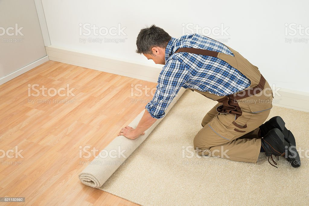 Worker Unrolling Carpet On Floor stock photo