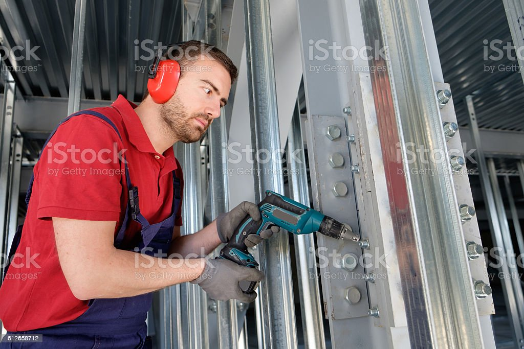 Worker using a drill in a construction site stock photo