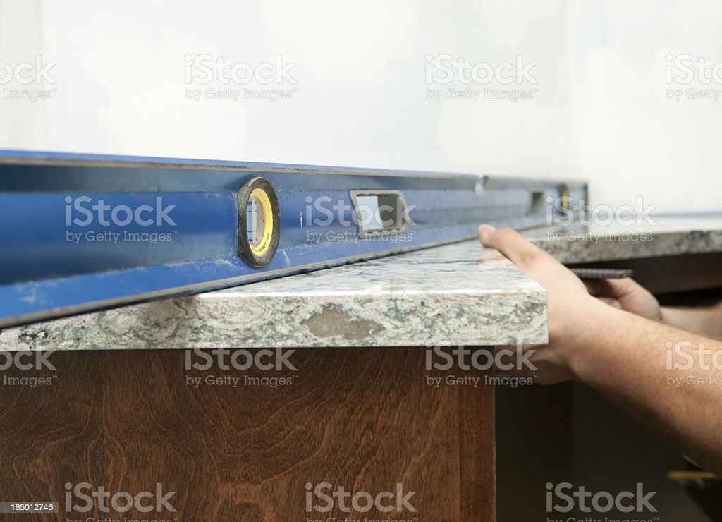 Worker Using a Level to Install Solid Surface Countertop stock photo