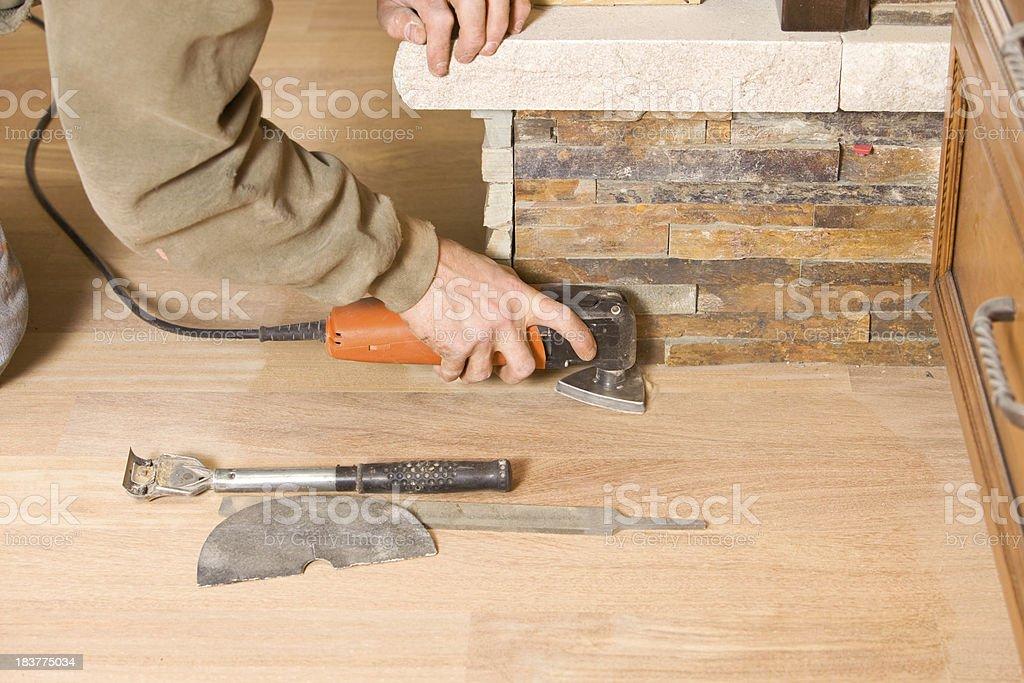 Worker Using a Multipurpose Sander on Hardwood Floor Edge stock photo