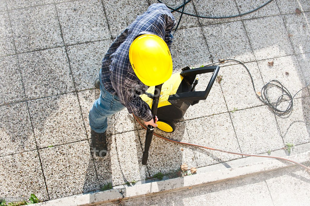 Worker using a pressure cleaner on a sidewalk stock photo