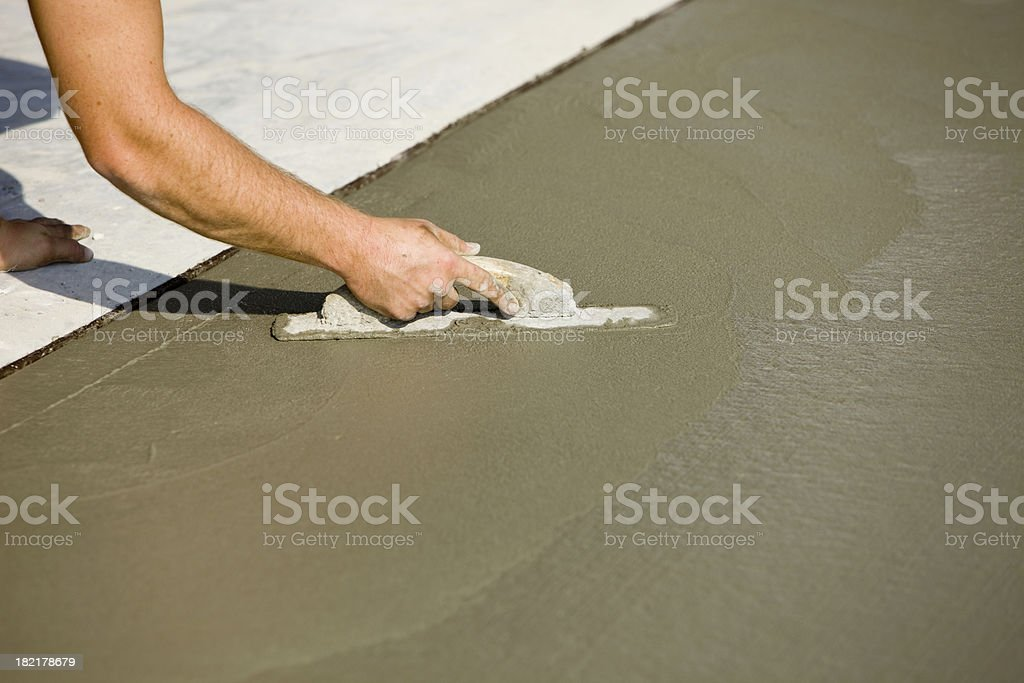 Worker Using Concrete Trowel to Smooth Driveway stock photo