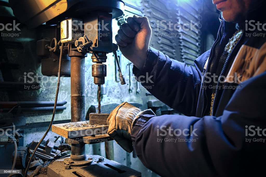 Worker using drill press in workshop stock photo