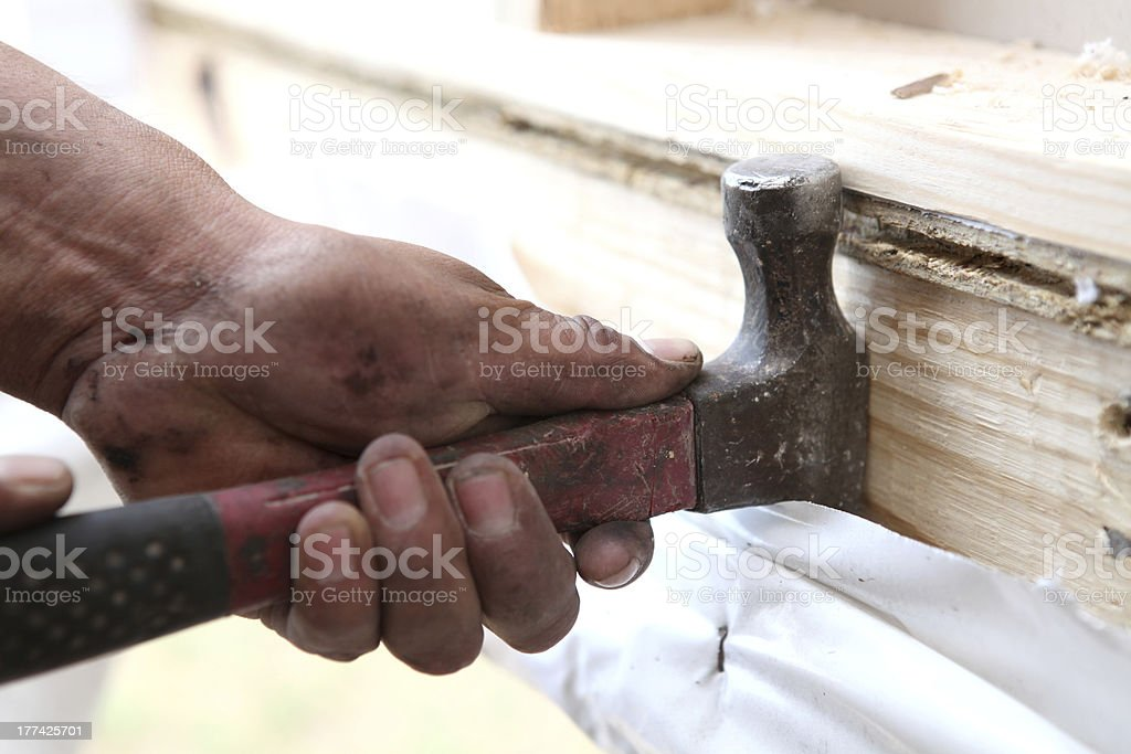 Worker Using Hammer To Pry Wood royalty-free stock photo