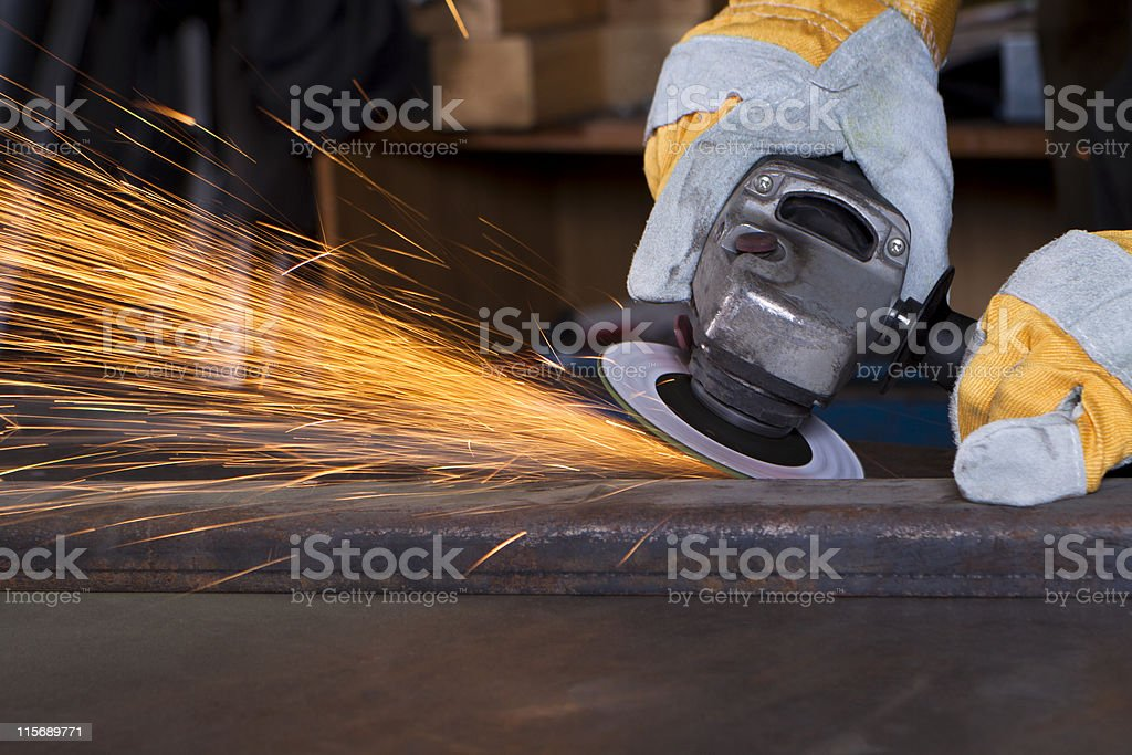 Worker using machine to grind metal stock photo