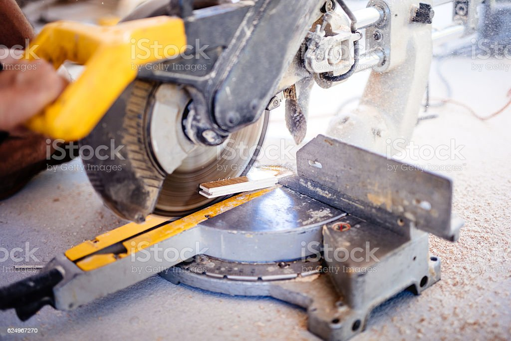 worker using mitre saw for cutting wood parquet stock photo