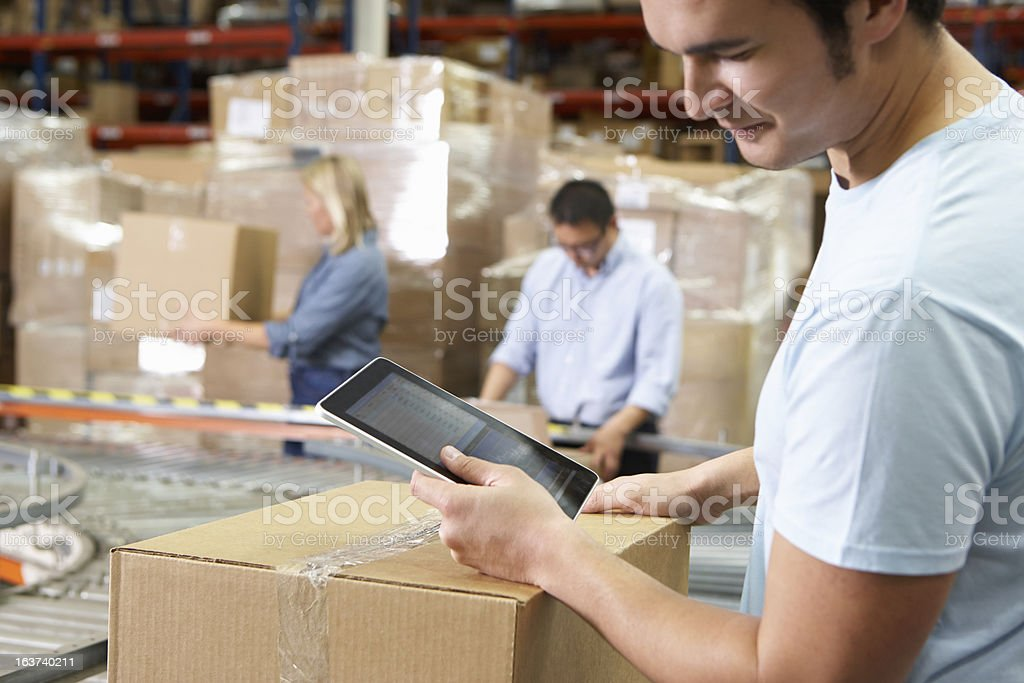 Worker Using Tablet Computer In Distribution Warehouse stock photo