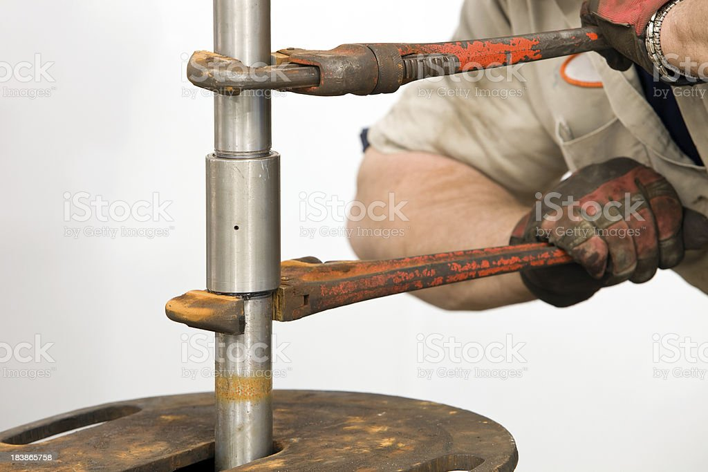 Worker Using Two Pipe Wrenches to Join Pump Drive Shaft stock photo