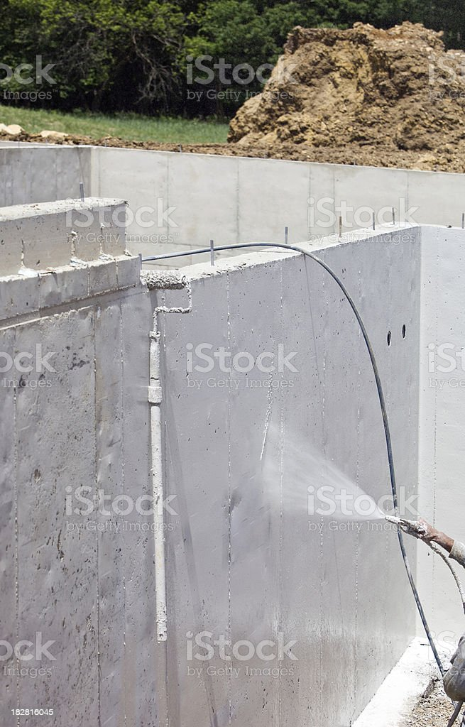 Worker Waterproofing a new Home Foundation stock photo