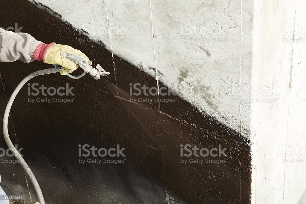 Worker Waterproofing a new House Foundation stock photo