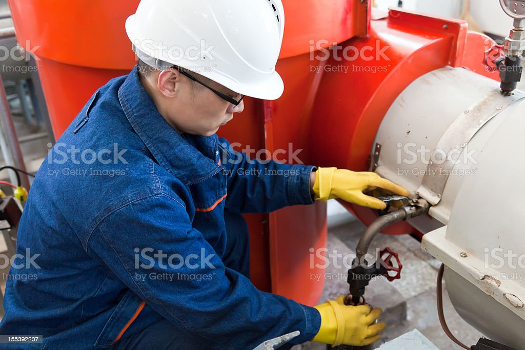 A worker wearing a hard hat collecting an oil sample  stock photo