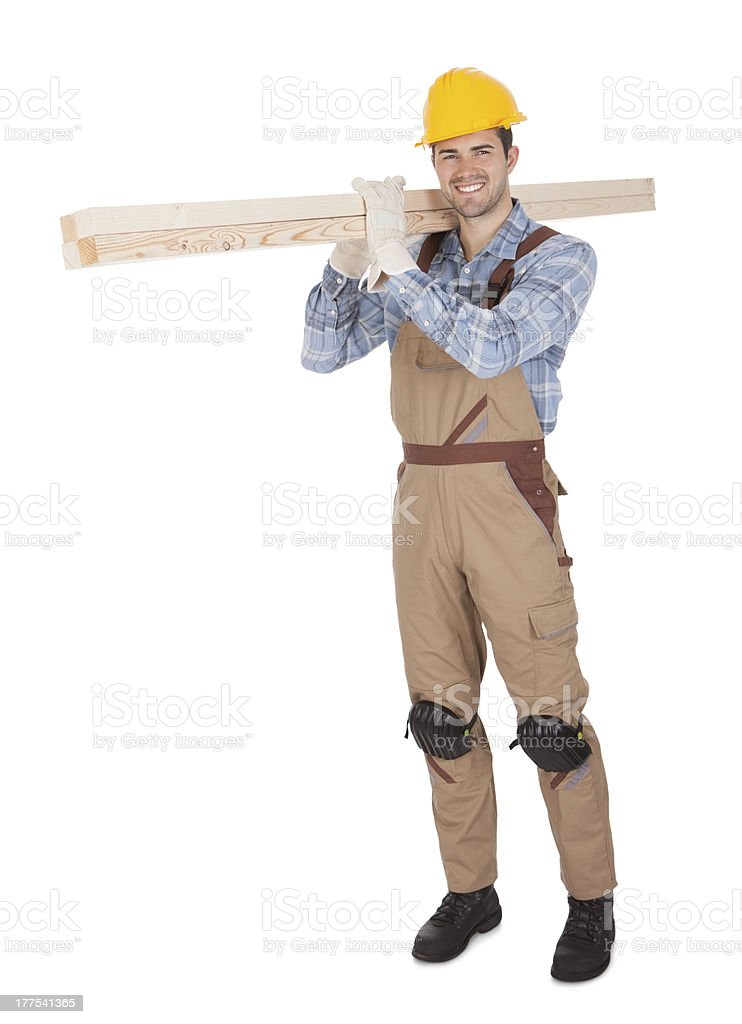 Worker wearing hard hat and carrying timber royalty-free stock photo