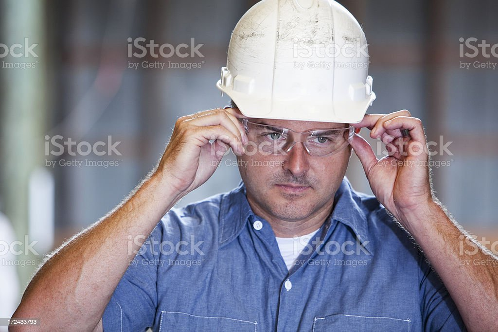 Worker wearing hard hat and safety glasses stock photo