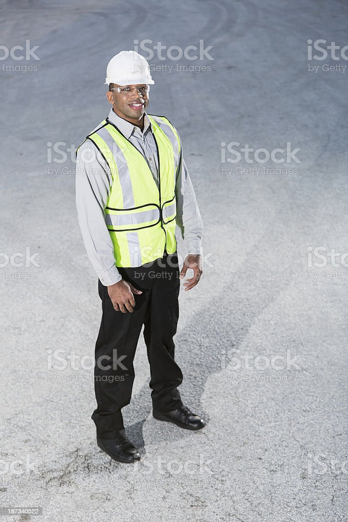 Worker wearing hardhat and safety vest stock photo