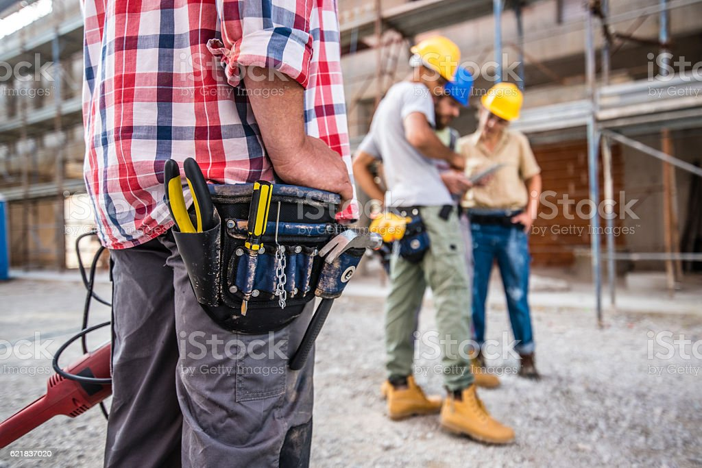 Worker wearing tool belt stock photo