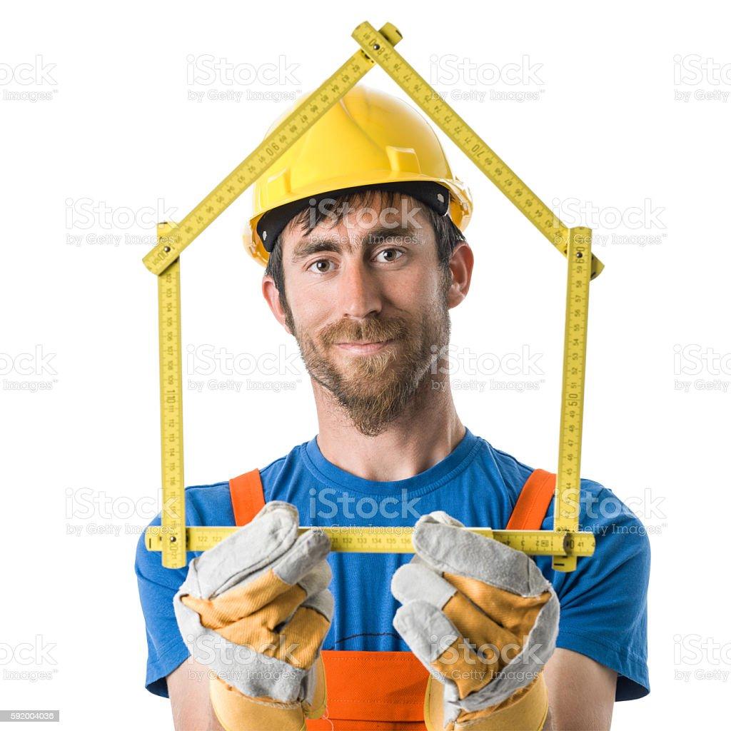 Worker Wearing Yellow Helmet Holding Meter In Shape Of House stock photo
