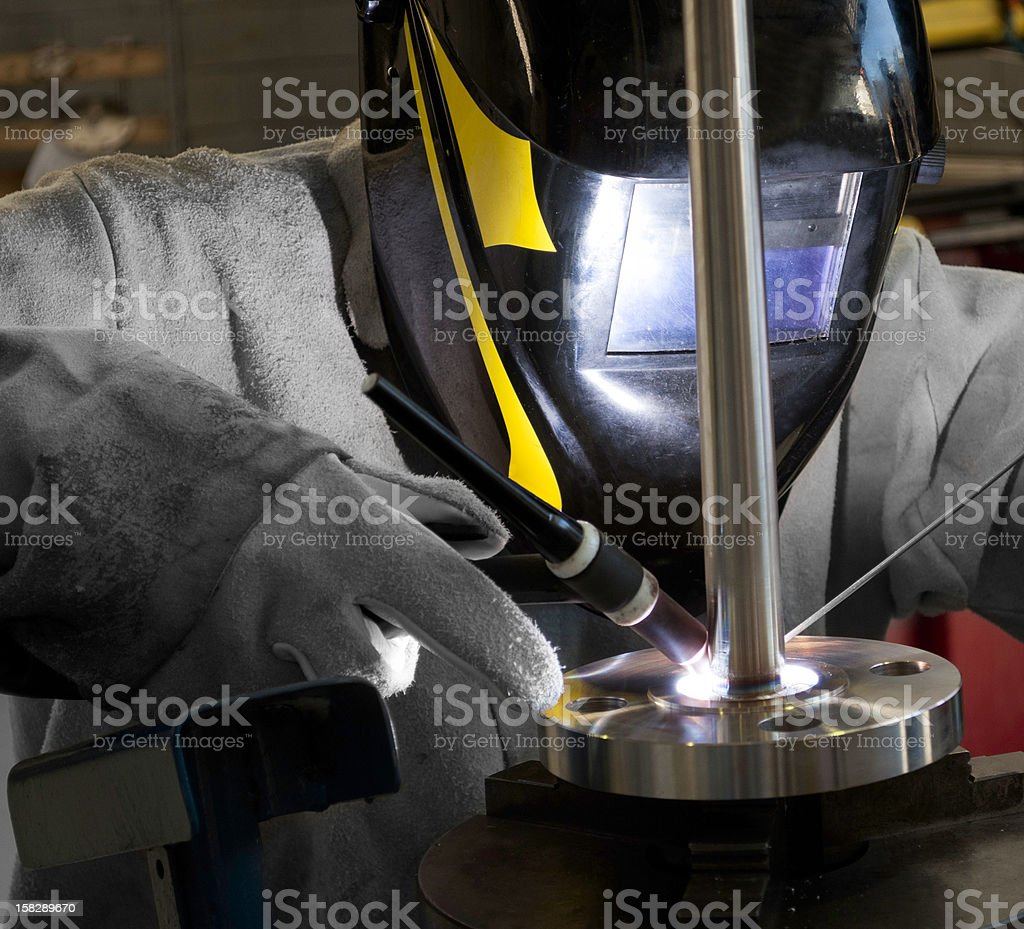 Worker welding a flanged well (Thermocouple) royalty-free stock photo
