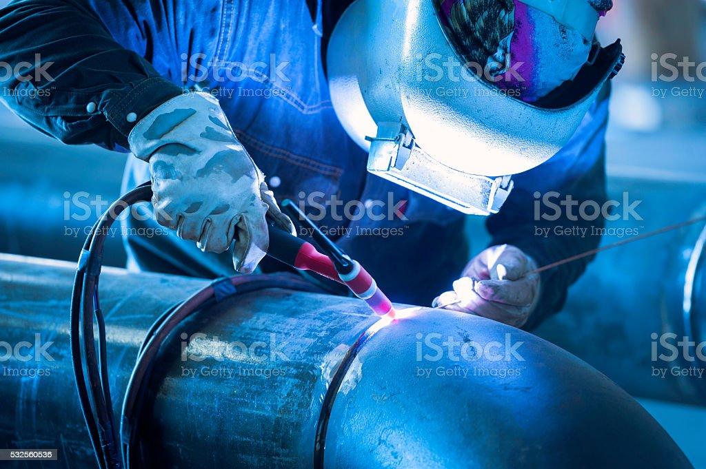 Worker welding metal piping using tig welder stock photo