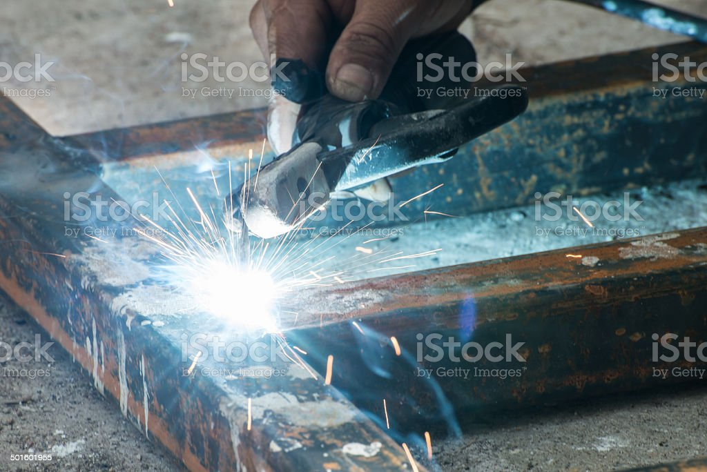 Worker welding steel with sparks lighting stock photo
