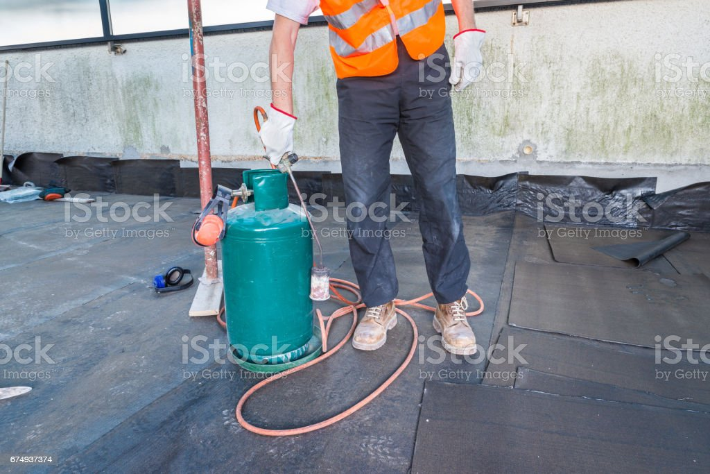 Worker, with a roofing gas torch, is installing rolls of bituminous waterproofing membrane for the waterproofing of a terrace - roof of a home stock photo