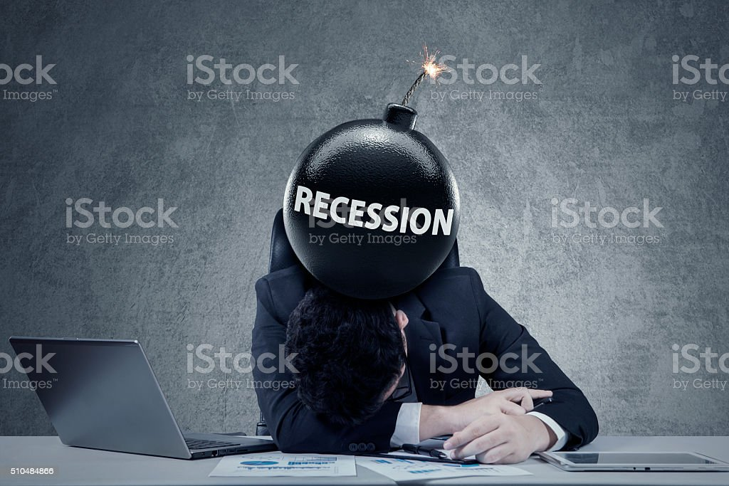 Worker with bomb of economic recession stock photo