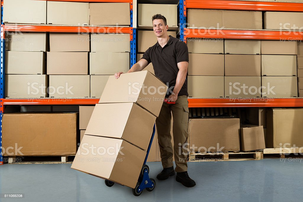Worker With Boxes On Hand Truck In Warehouse stock photo
