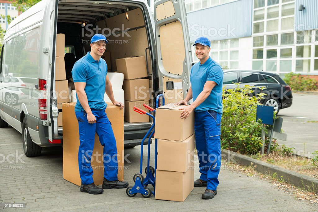 Worker With Cardboard Boxes In Front Of Truck stock photo