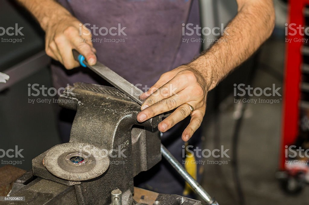 Worker with clamp and rasp at tool workshop. stock photo