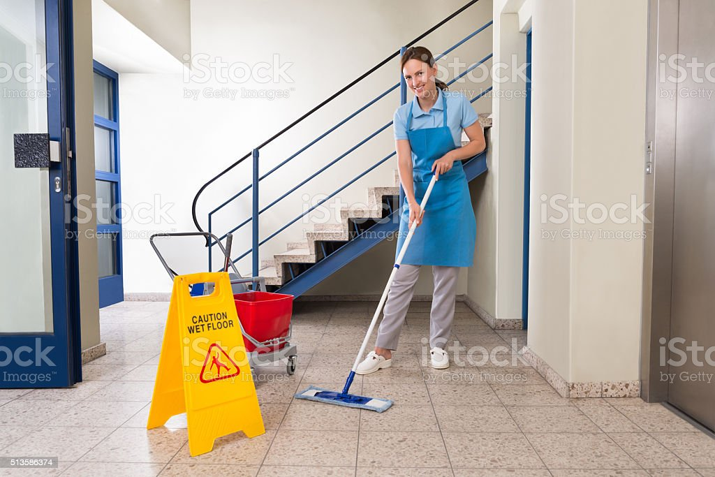 Worker With Cleaning Equipments And Wet Floor Sign stock photo