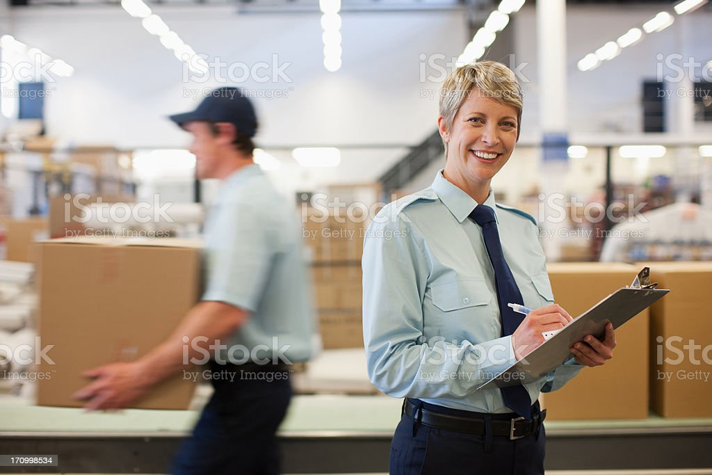 Worker with clipboard in shipping area stock photo