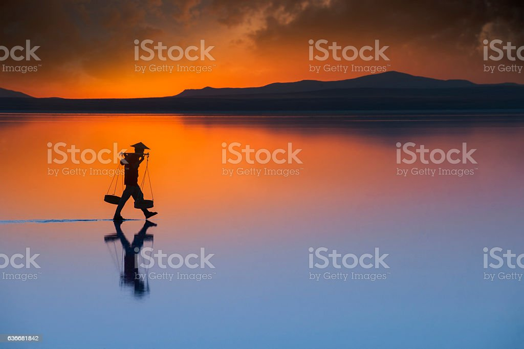 worker with conical straw hat, carrying salt on the water stock photo